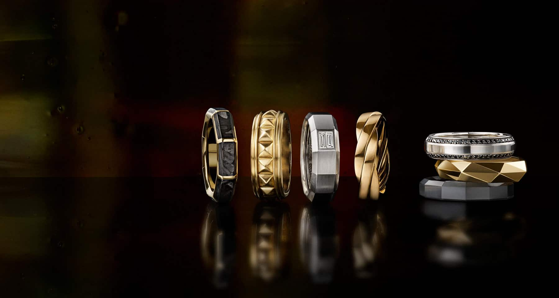 A color photo shows a vertical stack of three David Yurman men's bands to the right of a horizontal row of four David Yurman men's bands—all placed on a black reflective surface. Four of the men's rings are crafted from 18K yellow gold with or without forged carbon. Two of the rings are crafted from 18K white gold with black or white diamonds. The final ring is crafted from black titanium