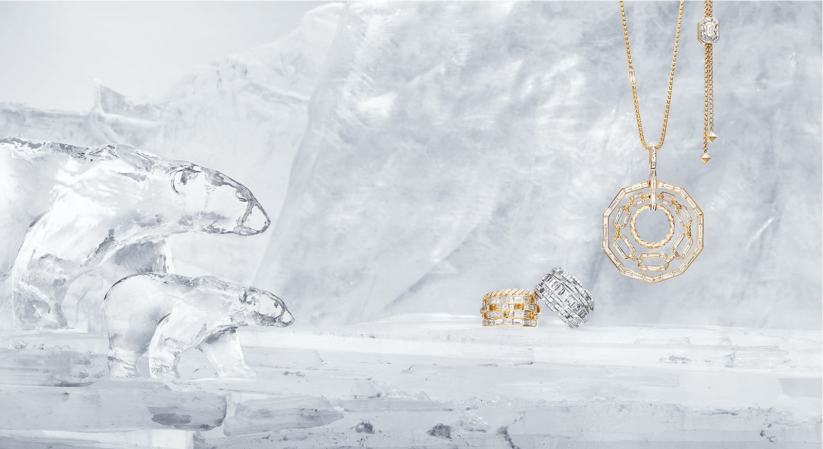 Two polar bear ice sculptures look across a frozen landscape at two Stax rings in 18K yellow or white gold with diamonds and a Stax pendant in 18K yellow gold with diamonds, all from the High Jewelry Collection.
