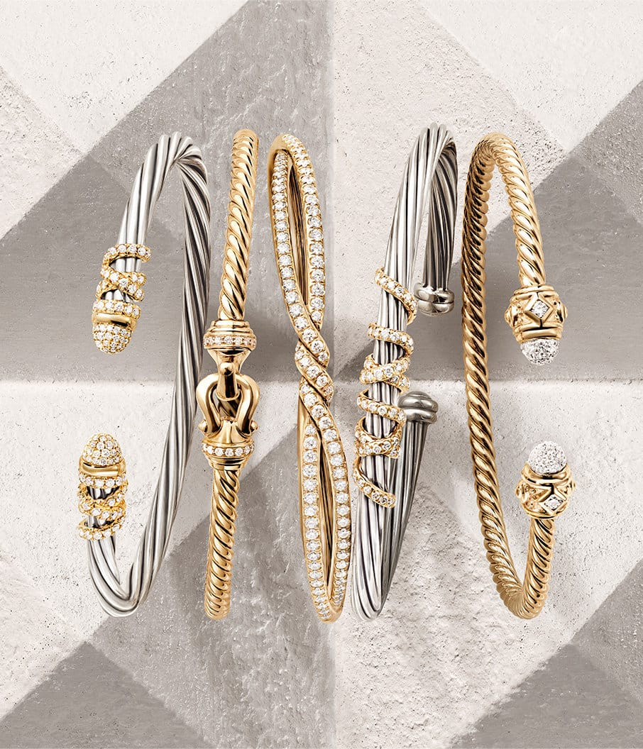 A color photo shows an overhead shot of a horizontal stack of five David Yurman bracelets from the Helena, Buckle, Continuance, and Renaissance collections leaning against each other on top of a beige-hued stone surface with pyramid-shaped protrusions. Three of the women's bracelets are crafted from 18K yellow gold with pavé white diamond accents. Two of the women's bracelets are crafted from 18K white gold encrusted with 18K yellow gold threads set with pavé white diamonds.