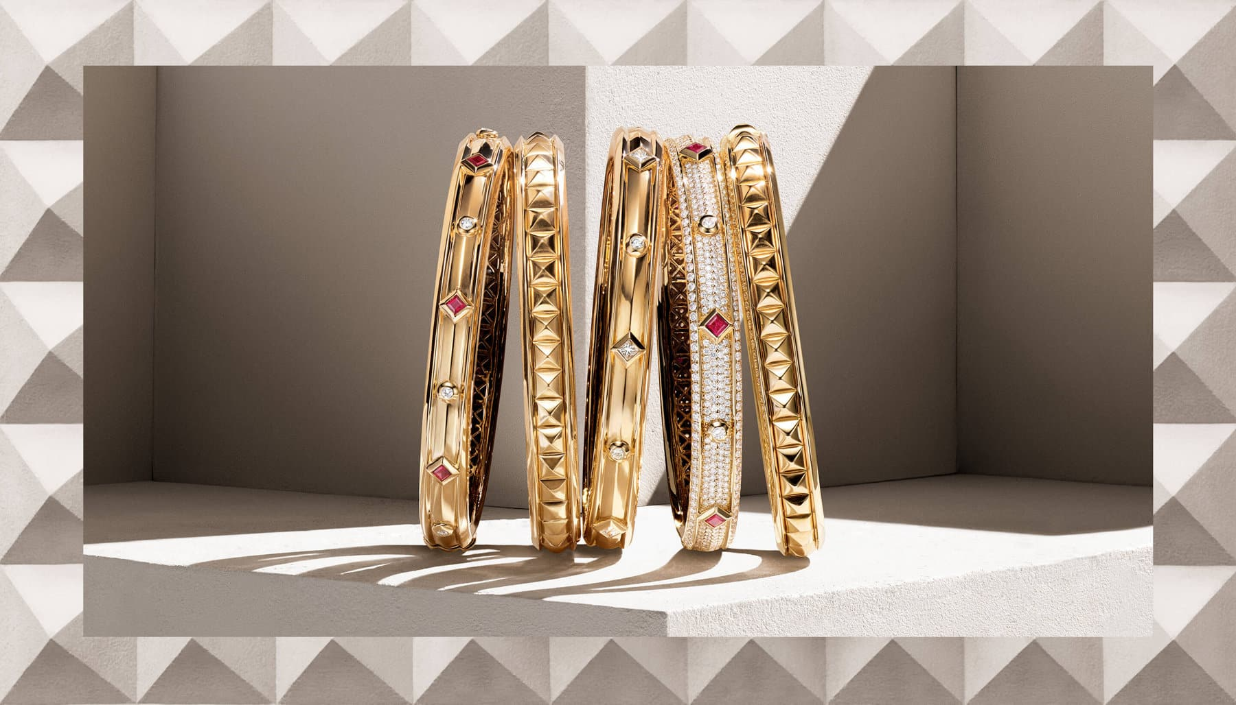 A color photo shows a horizontal stack of five David Yurman bracelets from the Modern Renaissance Collection leaning against each other on top of a beige-hued stone shelf with diagonal shadows. The women's jewelry is crafted from 18K yellow gold with or without white diamonds and rubies. This photo is juxtaposed over a color photo of a beige stone surface with pyramid-shaped protrusions.