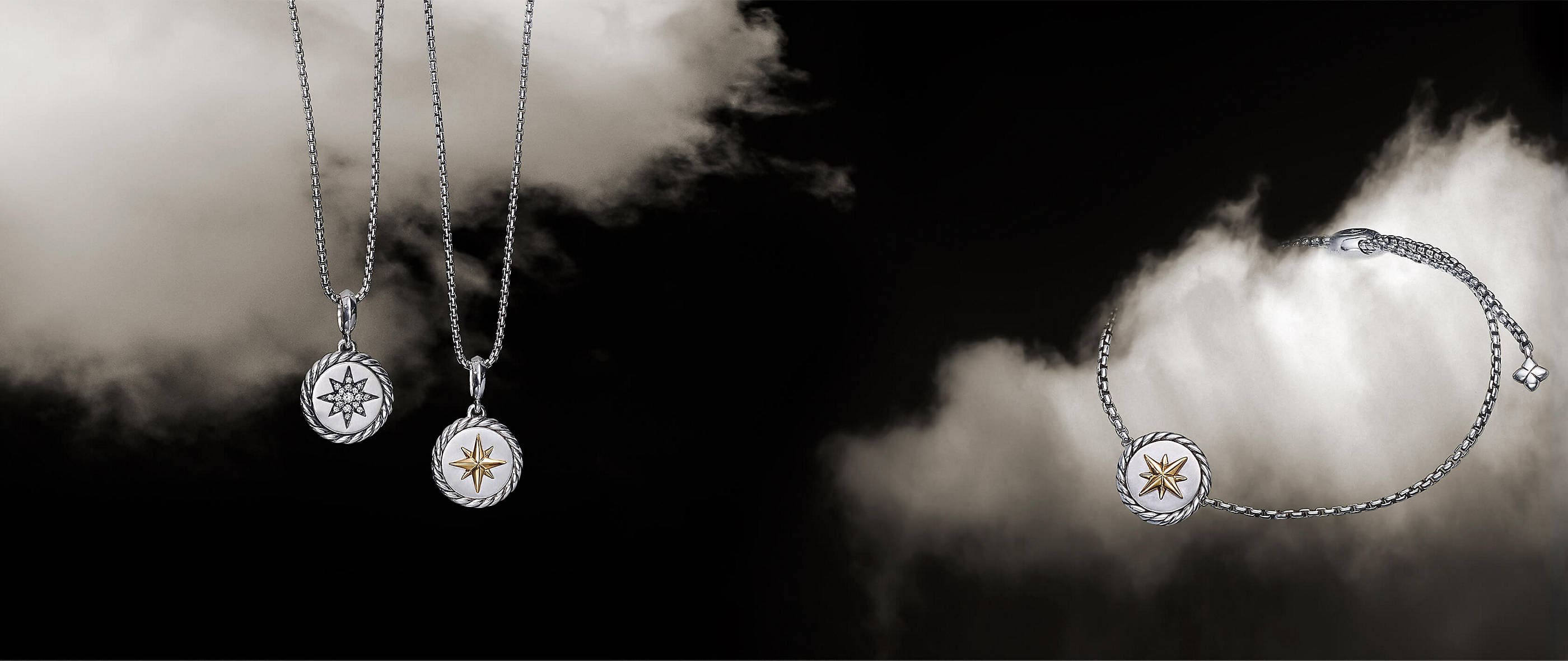 A color photograph two David Yurman women's North Star pendant necklaces hanging in front of a white cloud next to a North Star bracelet floating on a white cloud in a starry night sky. The jewelry is crafted from sterling silver with star-shaped diamond accents or sterling silver with star-shaped 18K yellow gold accents.