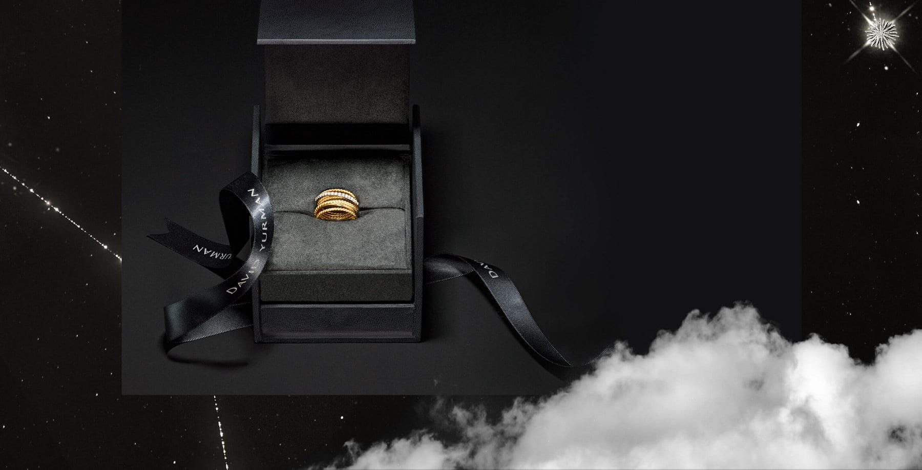 A color photo shows a David Yurman black ring box on a black background. This image is collaged in the center of a starry night sky with a white cloud.