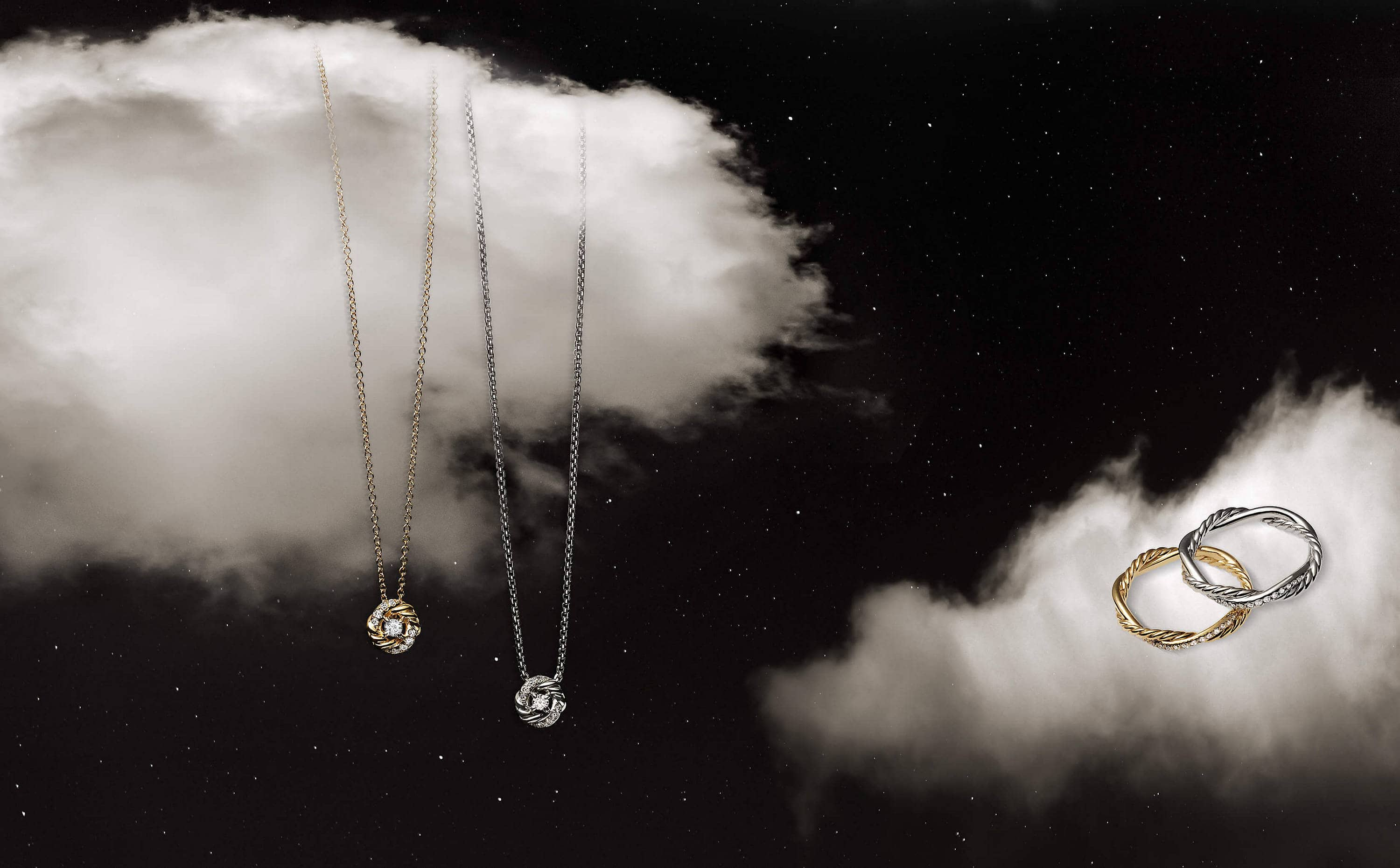 A color photo shows two pendant necklaces floating in front of a could next to a pair of band rings on a cloud from the David Yurman women's Infinity Collection in front of a starry night sky. The jewelry is crafted from strands of sterling silver or 18K yellow gold Cable entwined with pavé diamonds.