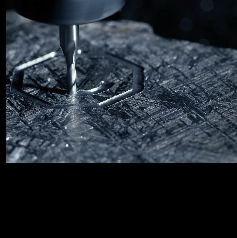 A close-up of a meteorite being etched with a hallmark.