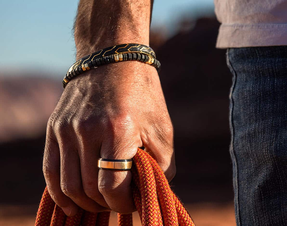 A color photo shows a man's hand holding orange ropes outdoors while wearing two David Yurman bracelets and a ring from the Forged Carbon, Hex and Beveled collections. The jewelry is crafted from 18K yellow gold with or without forged carbon or black titanium