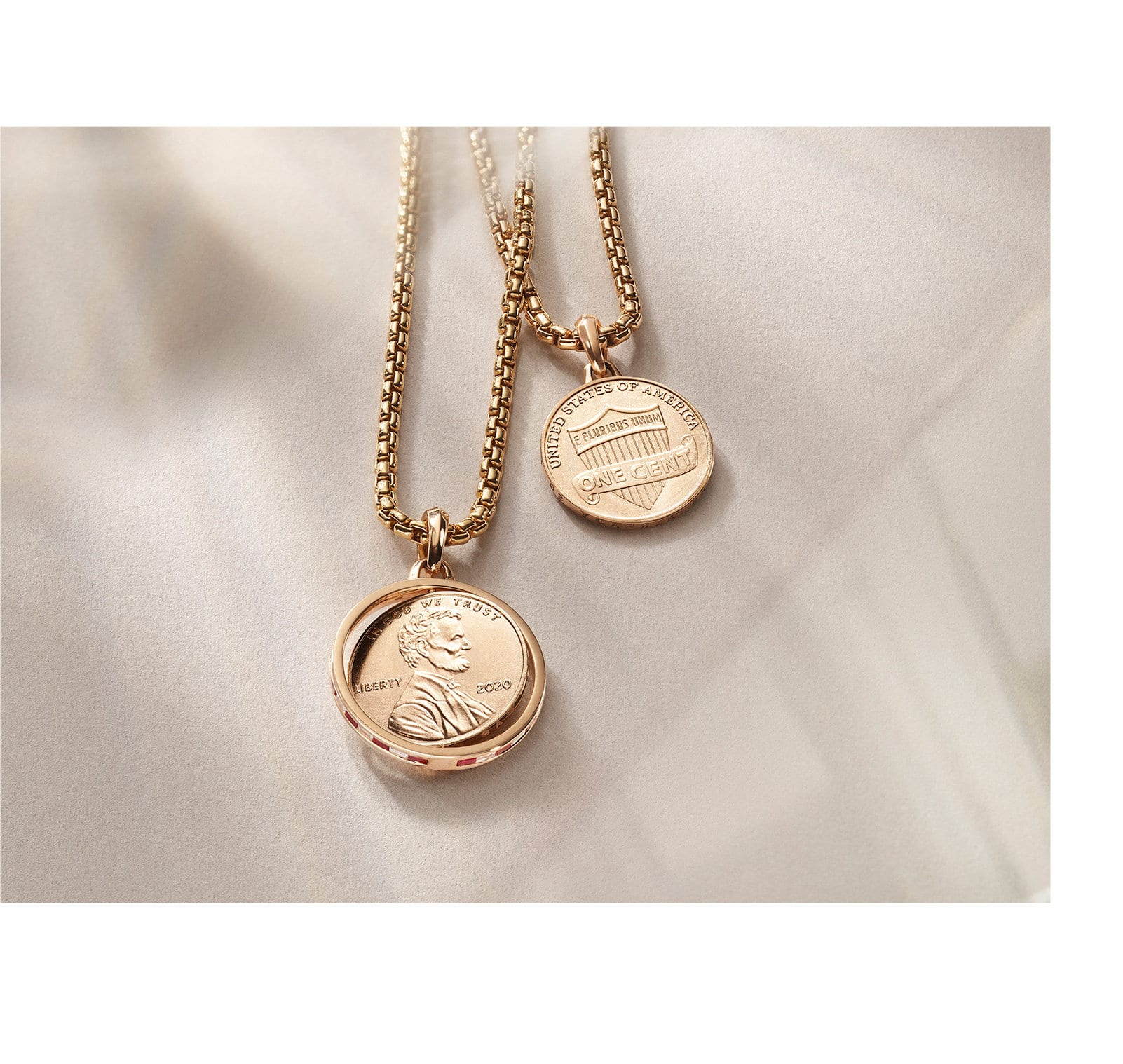 An image showing two David Yurman x Jill Magid penny amulets strung on box chains. The jewelry is crafted from 18K rose gold with or without ruby and diamond baguettes