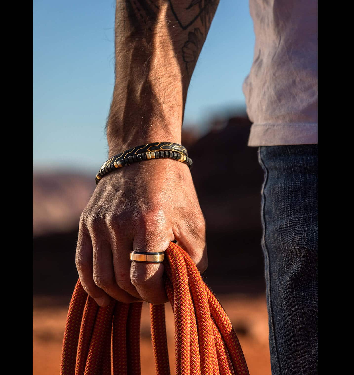A color photo and video are placed side by side. The photo shows a man's hand holding orange ropes outdoors while wearing David Yurman bracelets and a ring. The video shows Jimmy Chin taking pictures while climbing a large rock.