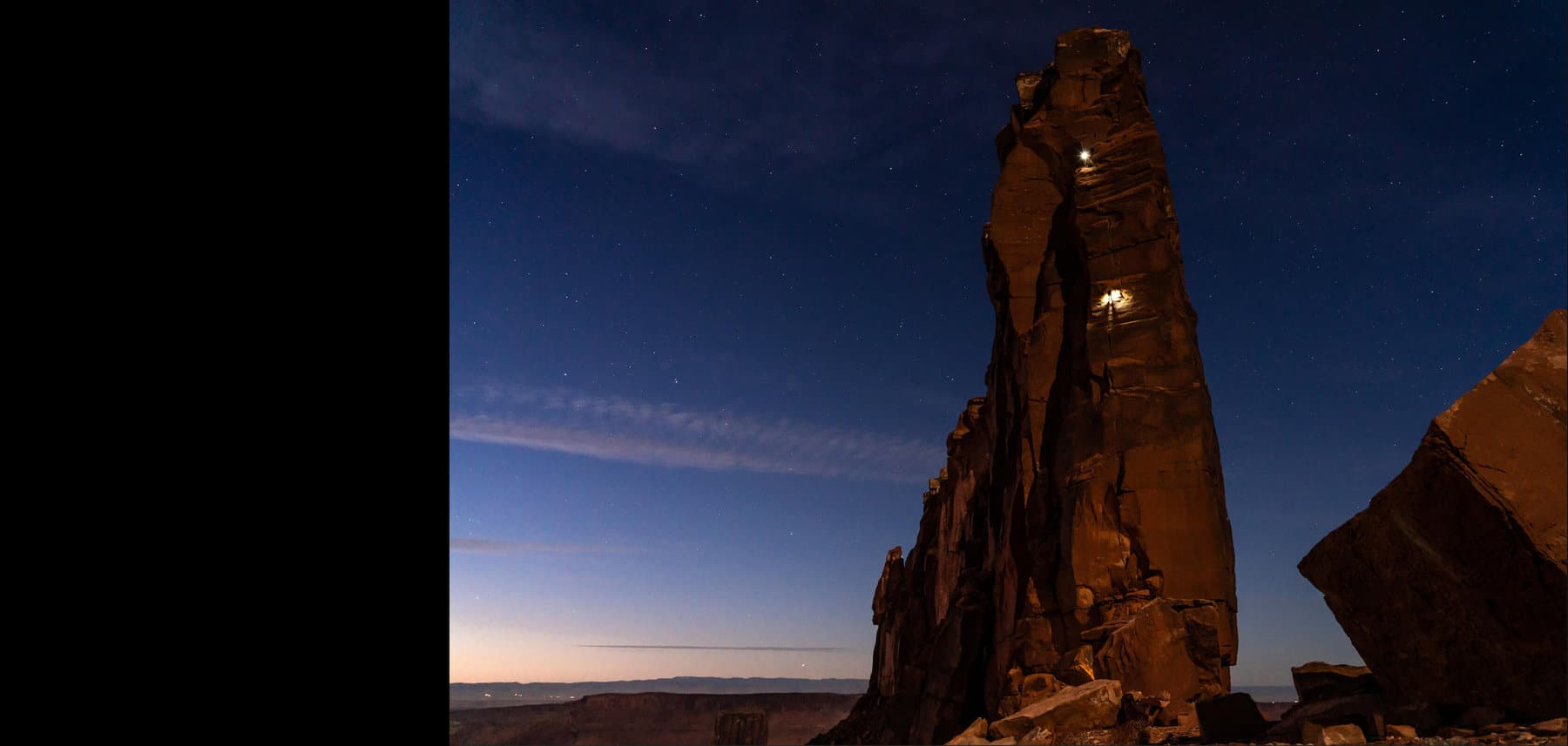 Below these two images is an image of a large rock tower lit by two lights at night.