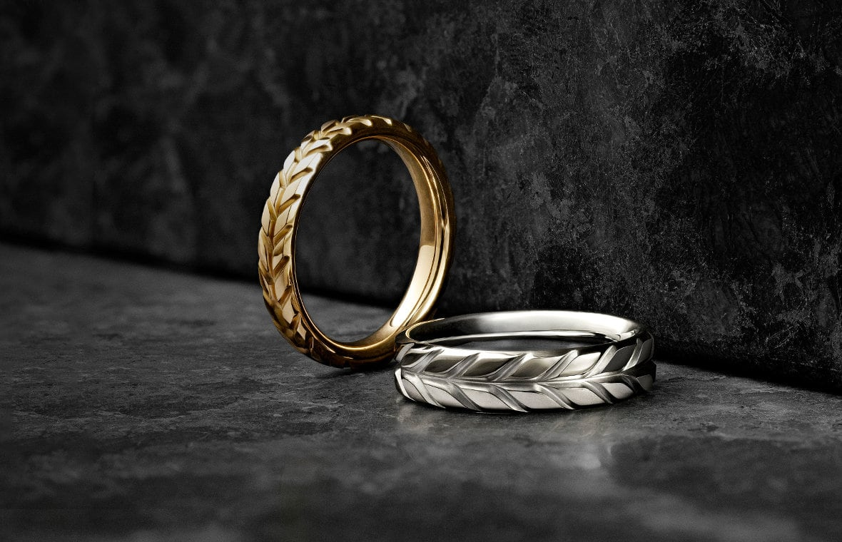 Two Chevron bands in 18K yellow or white gold in a row on the corner of a scratched, dark stone.