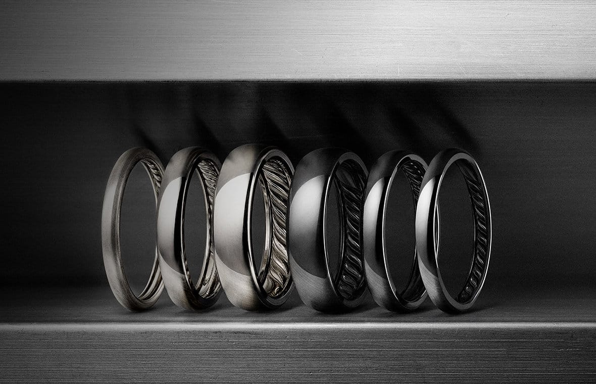 DY Classic bands in grey or black titanium, and in three different widths, in a row between blocks of titanium.