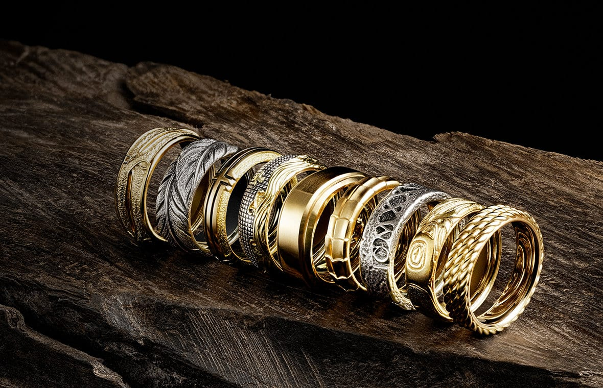 Armory, Southwest, Waves, Deco, Shipwreck, Northwest and Gator bands in 18K yellow gold and/or sterling silver, in a diagonal row on a dark, weathered wood log.