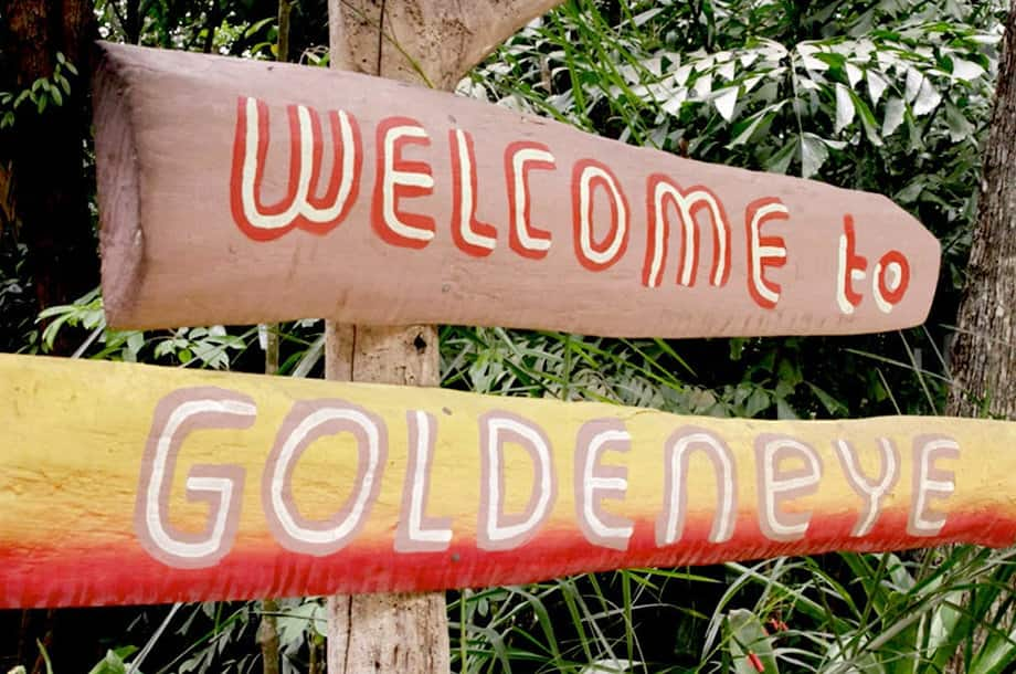 "A close-up of a wooden sign painted with ""Welcome to GoldenEye"" in a tropical forest."