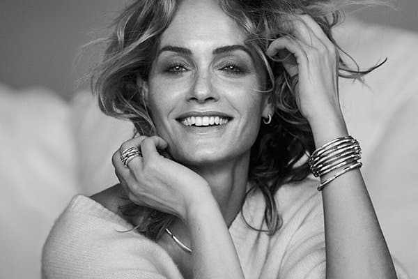 A black-and-white image of model Amber Valletta wearing a cream sweater and David Yurman Petite Pavé and Tides designs in sterling silver with white diamonds.