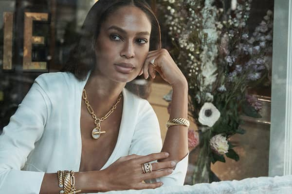 A color photo shows model Joan Smalls seated in a cafe looking through a window with a large floral arrangement to her right. She's wearing a white top and David Yurman Cable bracelets, a Lexington chain strung with a DY Elements mother-of-pearl amulet, a pinky ring and a Stax ring. The jewelry is crafted from 18K yellow gold with or without pavé diamonds.