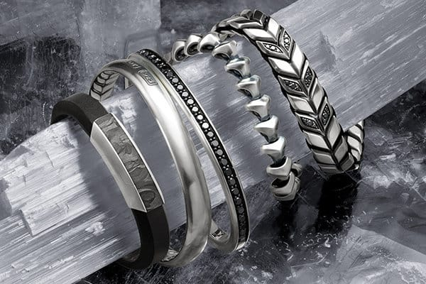 Forged Carbon, Streamline®, Armory® and Chevron bracelets in sterling silver or leather with or without forged carbon or pavé black diamonds, wrapped around a thin, jagged slab of ice.
