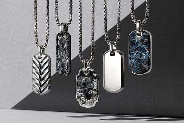 A color photo shows five men's tags and chains atop a grey background. Each design is from the Chain, Streamline, Forged Carbon, Waves or Exotic Stone collection and crafted from sterling silver with or without forged carbon or pietersite.