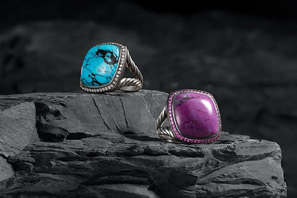 David Yurman Albion rings in sterling silver with turquoise and pave diamonds or sugilite and pink sapphires on a dark stone background.