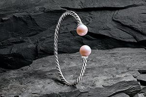 A Solari bracelet in sterling silver with cultured pink pearls and pavé white diamonds on a textured stone.