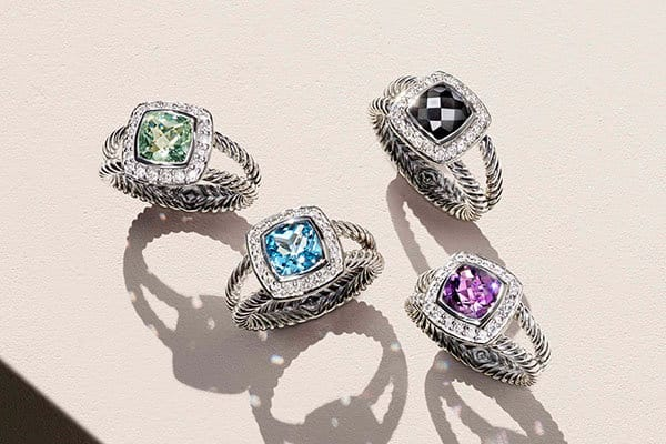 A color photograph shows four Petite Albion rings crafted from sterling silver with diamonds and prasiolite, blue topaz, black onyx or amethyst.