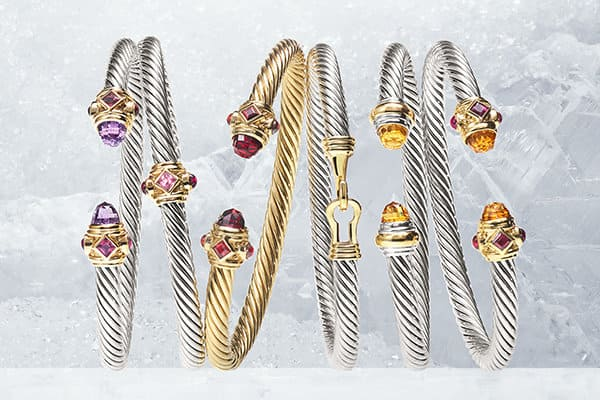 An array of David Yurman Renaissance, X Collection, Buckle and Cable Collection bracelets in sterling silver and 18K gold with a chromatic array of colored gemstones shot against a backdrop of ice.