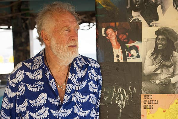 A color photograph of Chris Blackwell standing next to a wall covered with photos of Bob Marley.