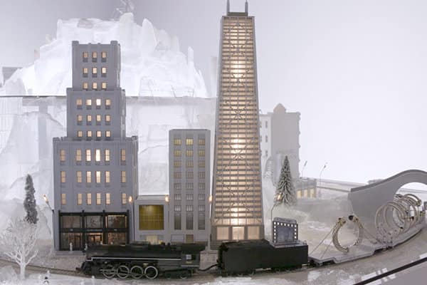 A still image from a video of a David Yurman model train traveling through a translucent white landscape and illuminated model city.