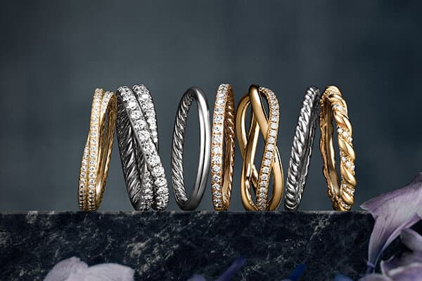 A color photograph shows a row of seven David Yurman wedding bands from the DY Crossover, DY Eden, DY Wisteria and DY Unity collections atop a dark, marbled stone surface with a dark background and flowers in the foreground. Each ring is crafted from 18K yellow or rose gold, or platinum, with or without pavé diamonds.