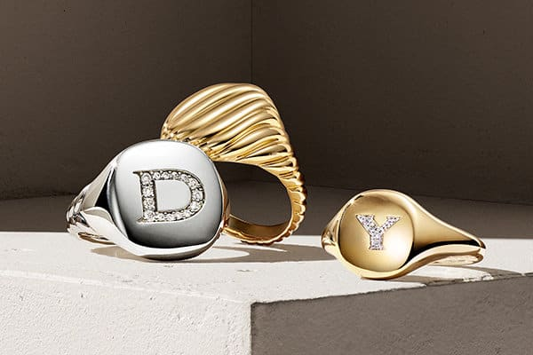 "A color photograph shows three David Yurman Cable Collectibles pinky rings atop a beige surface. Each ring is crafted from sterling silver or 18K yellow gold with or without pavé white diamonds forming the initial ""D"" or ""Y."""