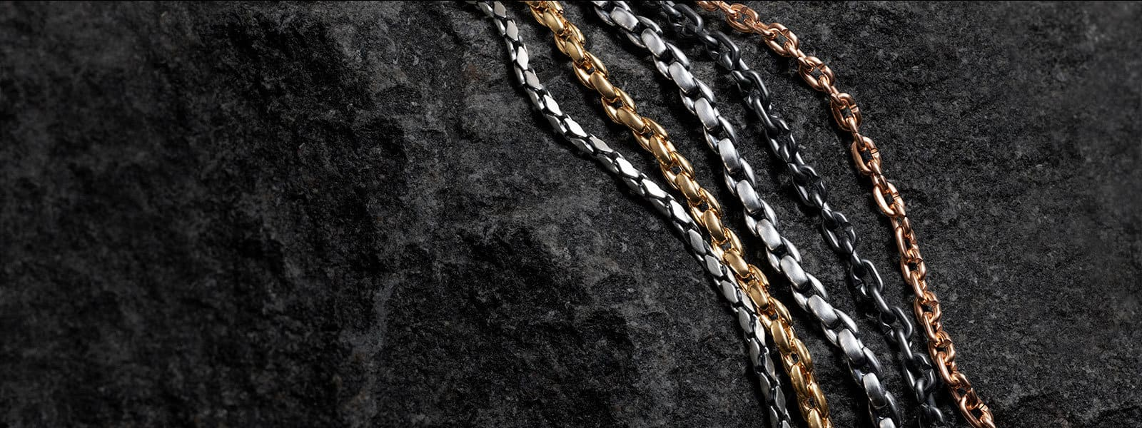 Fluted-chain necklace in sterling silver, elongated box-chain necklaces in 18K yellow gold and sterling silver and link-chain necklaces in black titanium with sterling silver and 18K rose gold on a stone.