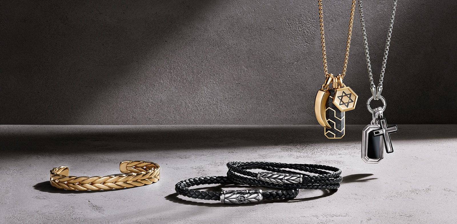 David Yurman Chevron bracelets, in 18K yellow gold or woven black rubber or leather with sterling silver, lying on a light grey stone surface next to hanging groups of David Yurman Roman, Forged Carbon and Deco amulets in 18K yellow gold or sterling silver with or without forged carbon or black onyx.