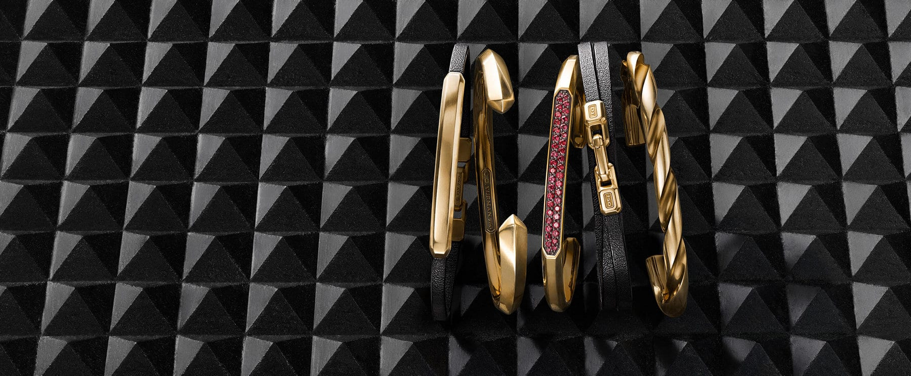 A color photograph shows an overhead shot of five David Yurman men's bracelets in a horizontal stack atop a charcoal-hued stone surface with pyramid-shaped protrusions. The bracelets are crafted from 18K gold. From left is a Streamline bracelet in black leather, a Roman cuff bracelet, a Streamline cuff bracelet with pavé rubies, a Streamline wrap bracelet in black leather and a Sculpted Cable cuff bracelet.