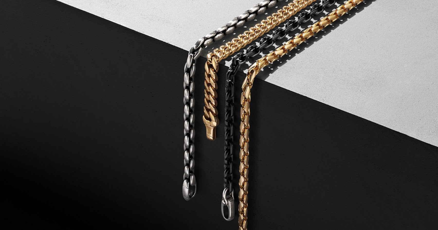 A color photo shows four David Yurman men's necklaces from the Chain collection arranged in rows next to each other draped over a gray concrete surface. Two box-chain necklaces are crafted from sterling silver or 18K yellow gold. One curb-link chain is crafted from 18K yellow gold. The final link-chain is crafted from black titanium with sterling silver.