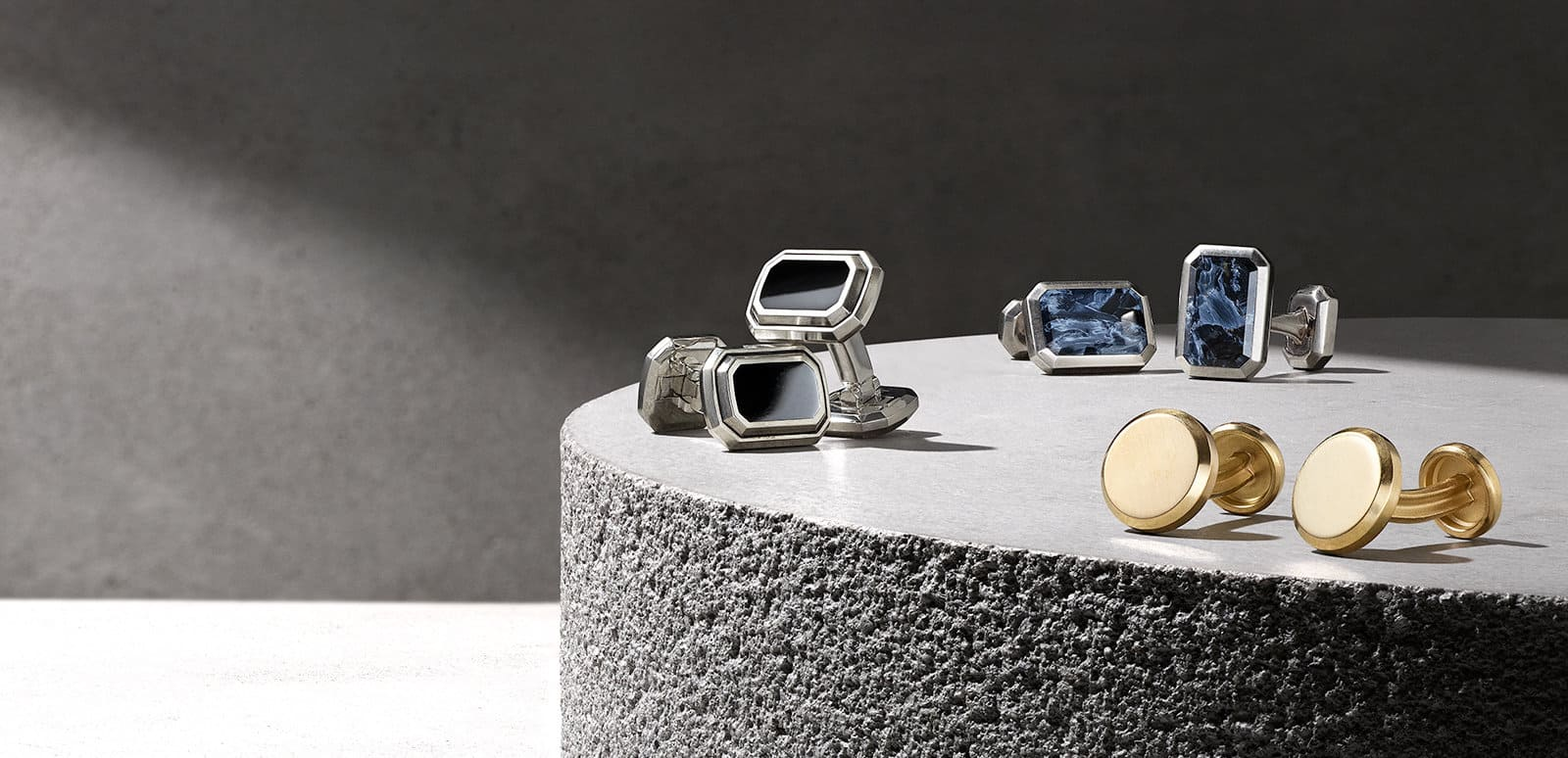 David Yurman Deco and Streamline cufflinks in sterling silver with black onyx or pietersite, or in 18K gold, in the light on top of a polished white stone with a curved, textured side.