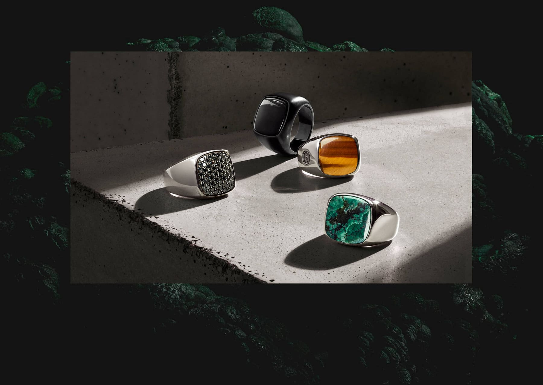 A group of David Yurman Exotic Stone signet rings in sterling silver with pietersite, red dinosaur agate and tiger's eye, laying on a light grey stone surface and casting long shadows.