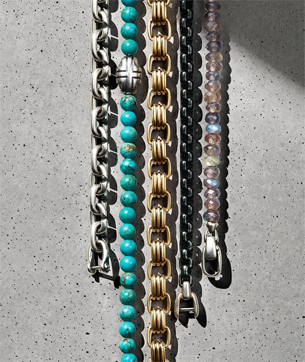 A row of David Yurman Chain, Spiritual Beads and Southwest bracelets in sterling silver, turquoise, 18K gold, black titanium with sterling silver and labradorite with sterling silver, laying on a light grey stone surface and casting long shadows.