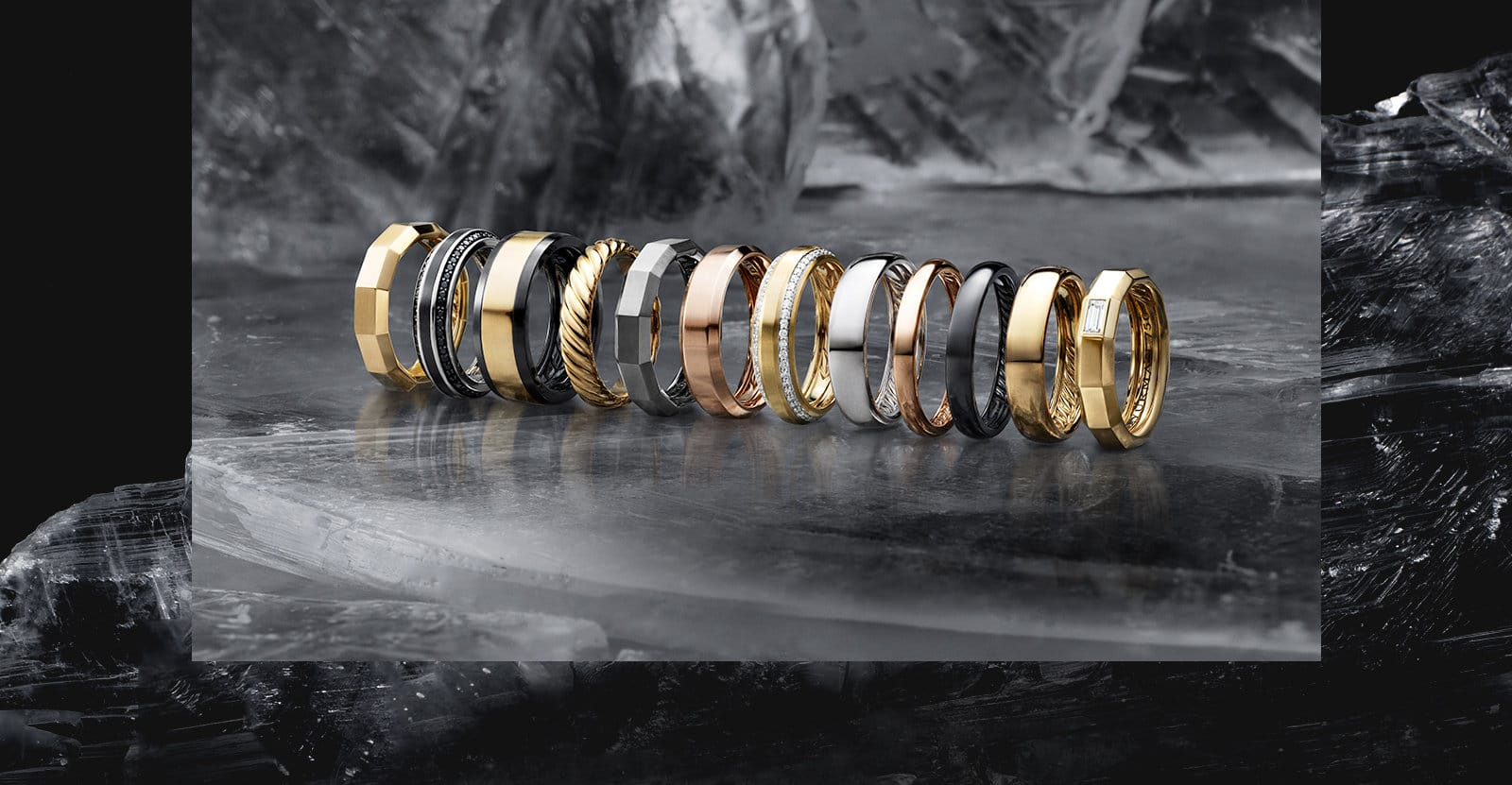 Men's bands in a variety of precious metals, titanium and diamonds in a row on a dark sheet of ice.