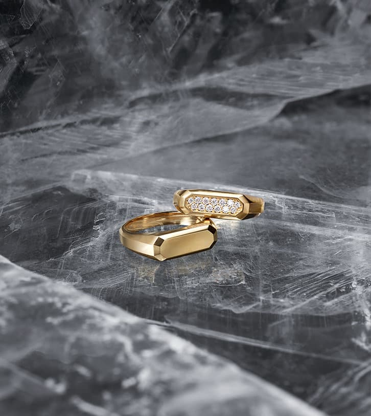 David Yurman men's Streamline® rings in 18K yellow gold with and without pavé diamonds shot against a backdrop of ice.