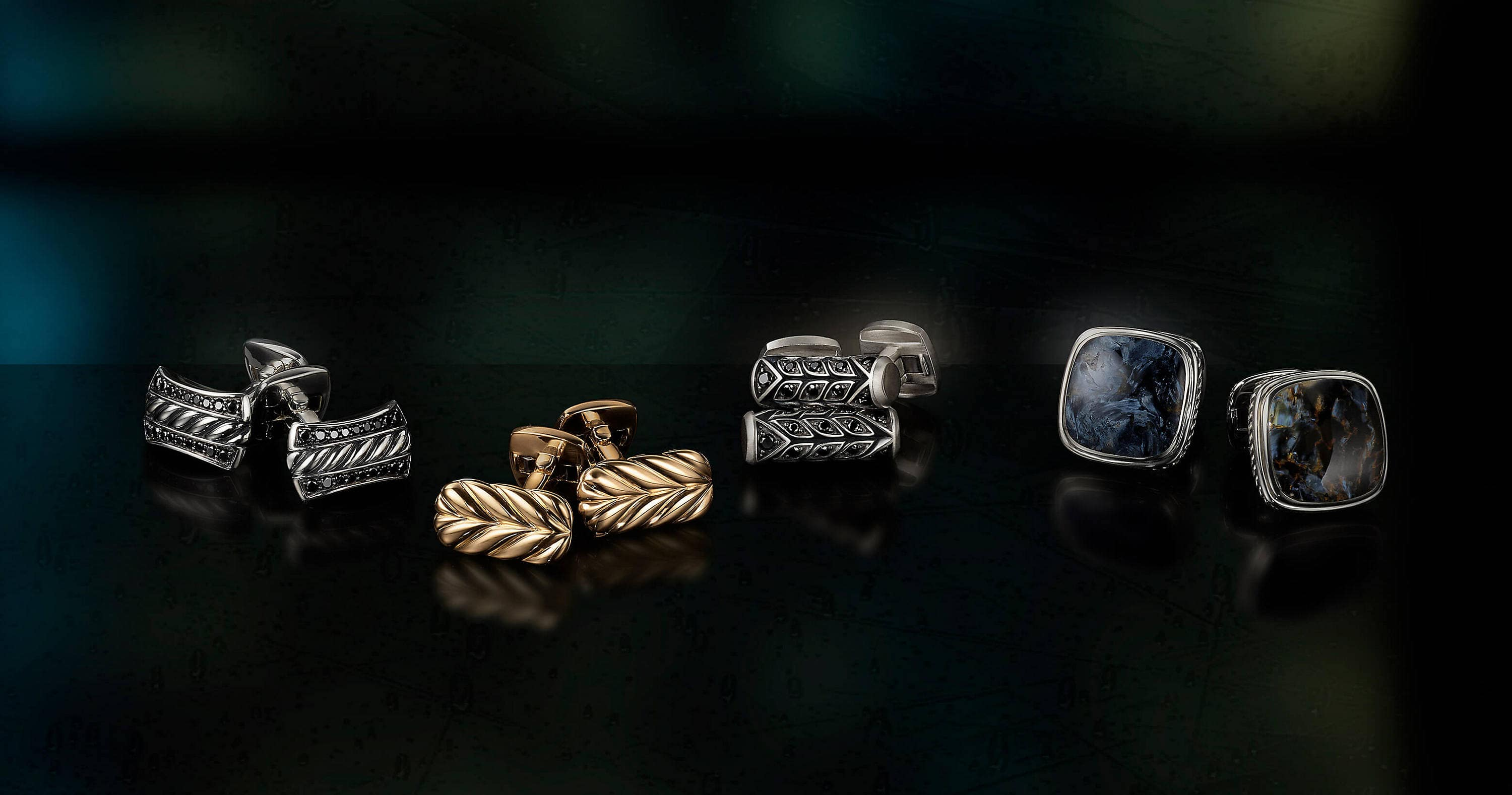 A color photograph shows four pairs of David Yurman men's cufflinks from the Cable, Chevron and Exotic Stone collections scattered on a black reflective surface with a colorful stained glass panel illuminated behind them. The men's accessories are crafted from sterling silver with pavé black diamonds, 18K yellow gold or sterling silver with pietersite.