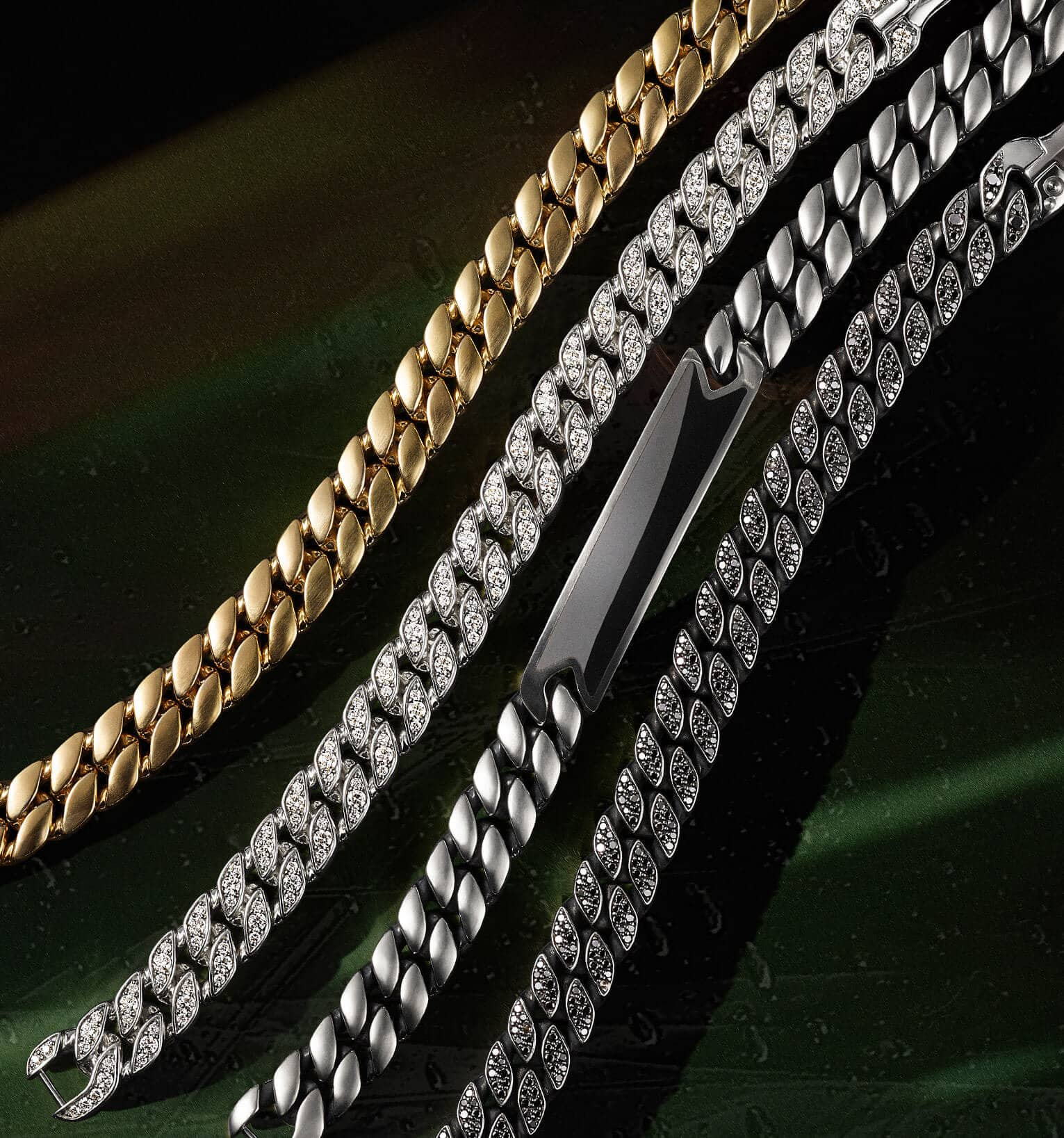 A color photograph shows a vertical row of four David Yurman men's curb chain bracelets atop a dark green backdrop illuminated by light. Three of the bracelets are crafted from sterling silver with or without white or black diamonds or black onyx. One bracelet is crafted from 18K yellow gold.