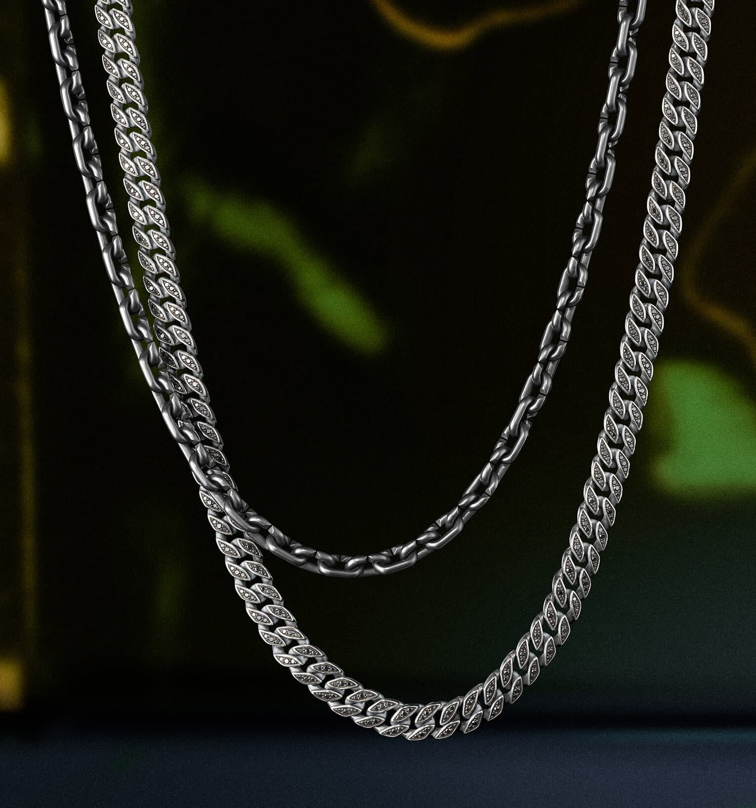 A color photo shows two David Yurman men's chain necklaces suspended in front of a colorful stained glass panel illuminated by light. One necklace is crafted from black titanium while the other is crafted from sterling silver with pavé diamonds.
