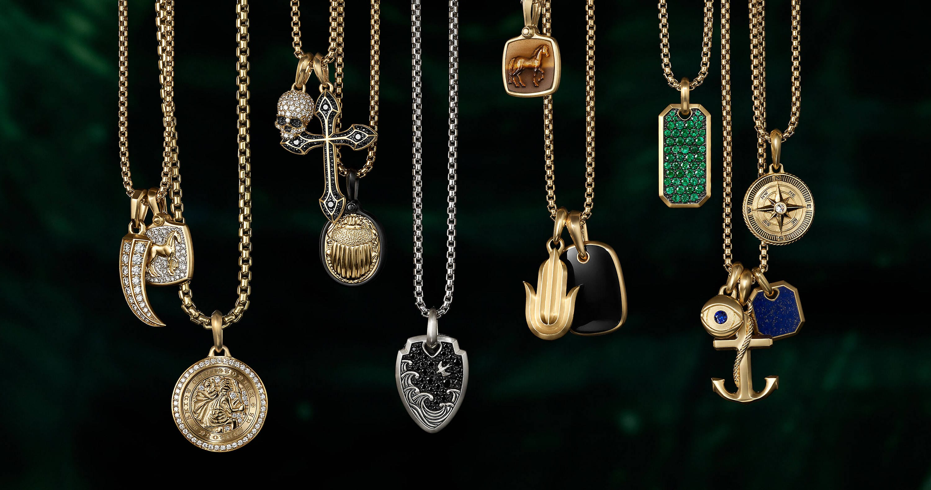 A color photograph shows a horizontal row of four David Yurman men's tags from the Streamline, Chevron and Pavé collections hanging on box-chain necklaces at different levels in front of gray concrete cubes with graphic shadows. The tags are crafted from sterling silver with 18K yellow gold, sterling silver with or without black onyx and black titanium with pavé black diamonds. The chains are crafted from 18K yellow gold, sterling silver or black titanium.