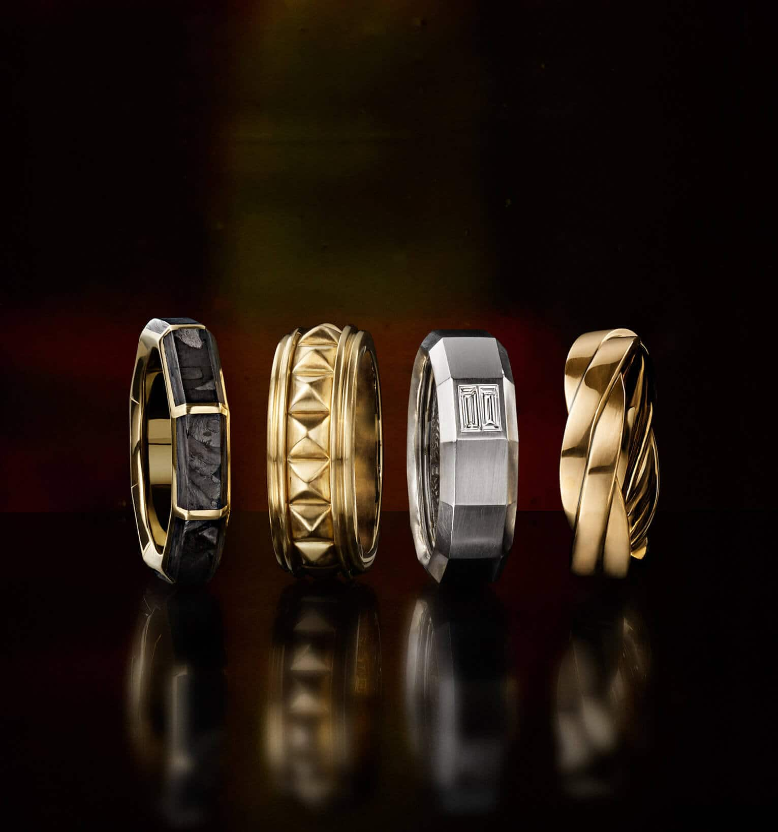 A color photo shows a horizontal row of four David Yurman men's bands—all placed on a black reflective surface. Three of the men's rings are crafted from 18K yellow gold with or without forged carbon. One ring is crafted from 18K white gold with white diamonds.
