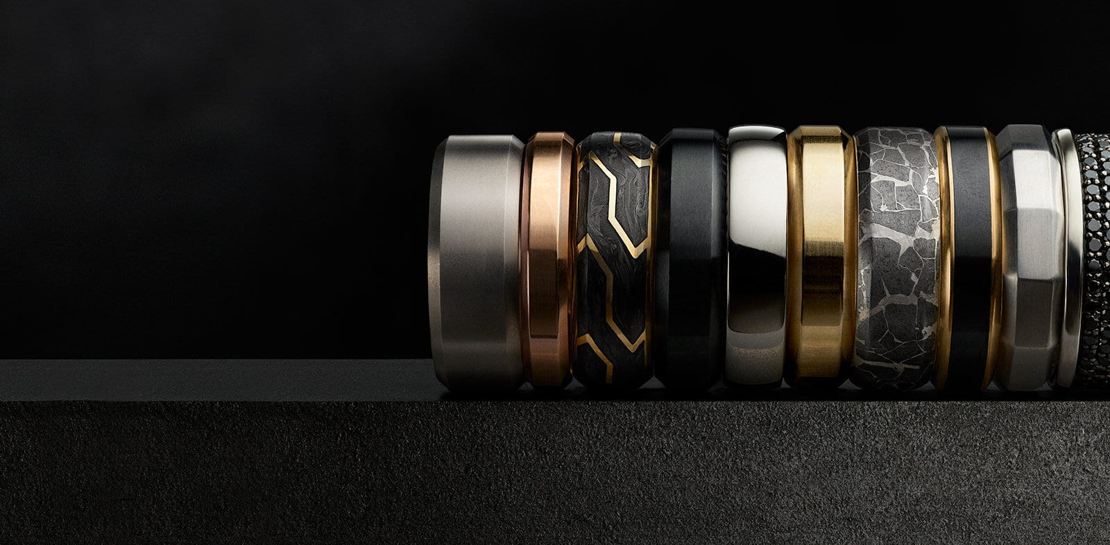 Various David Yurman men's bands in a multitude of materials on a stone.