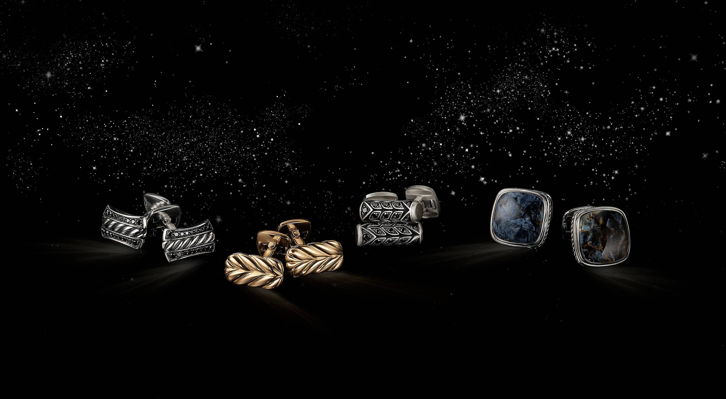 A color photograph shows four pairs of David Yurman men's cufflinks from the Cable, Chevron and Exotic Stone collections floating in a starry night sky. The men's accessories are crafted from sterling silver with pavé black diamonds, 18K yellow gold or sterling silver with pietersite.