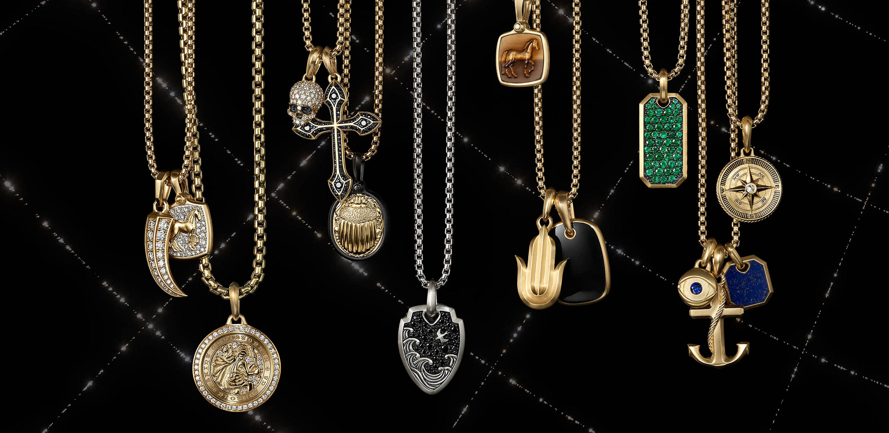 A color photograph shows 15 David Yurman amulet pendants strung on six box-chain necklaces suspended in front of a black background with white latitude and longitude lines. The men's pendants and necklaces are crafted from sterling silver or 18K yellow gold with or without pavé diamonds and an array of colored gemstones. The amulets come in various shapes such as a dog tag, horn, dagger, cross, anchor or depict a multitude of images such as a horse, compass rose, Hamsa hand, St. Christopher or a scarab.