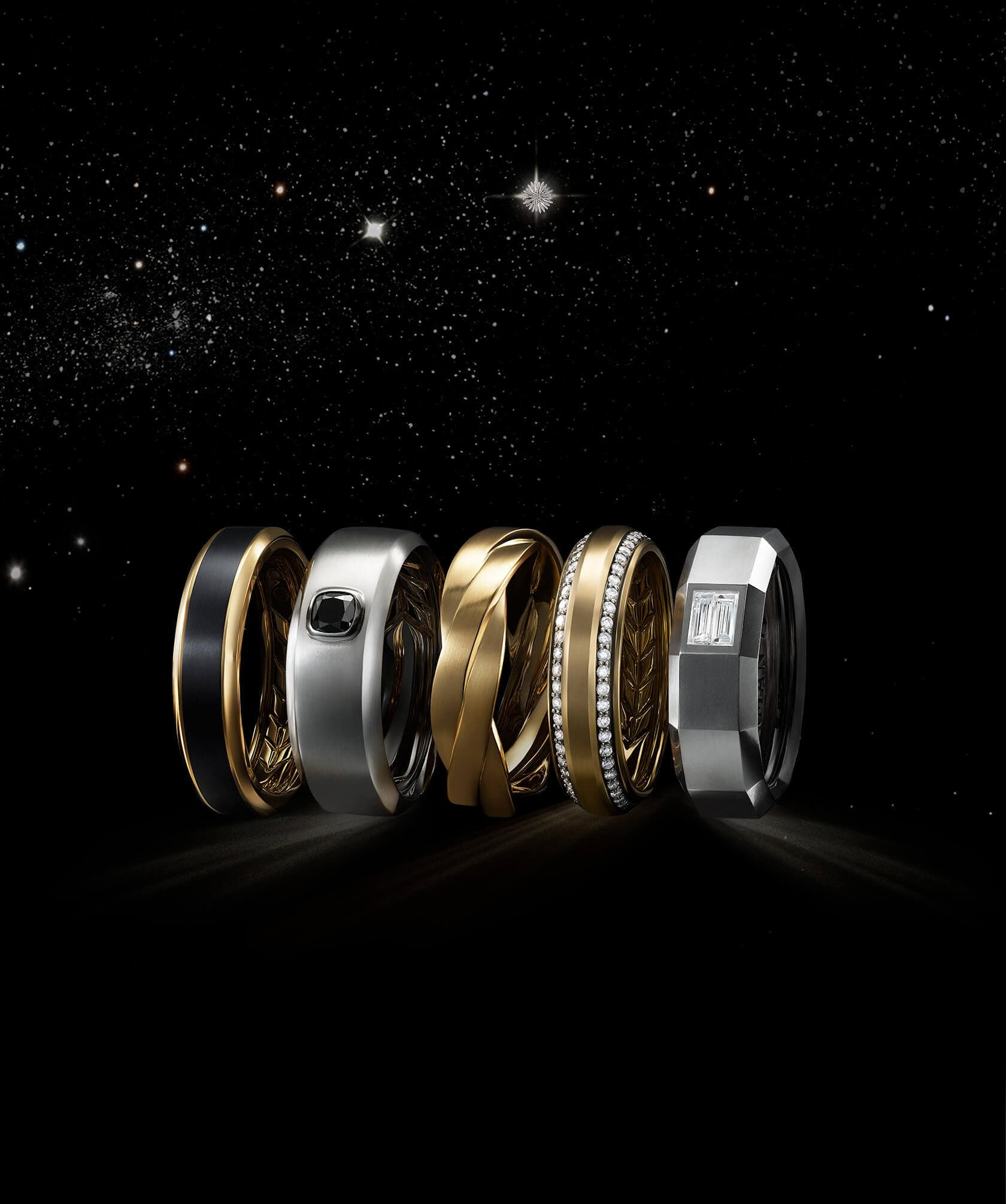A color photo shows a horizontal stack of five David Yurman men's bands floating in front of a starry night sky. Three of the men's rings are crafted from 18K yellow gold with or without pavé white diamonds or black titanium. Two of the rings are crafted from 18K white gold with or without black or white diamonds.