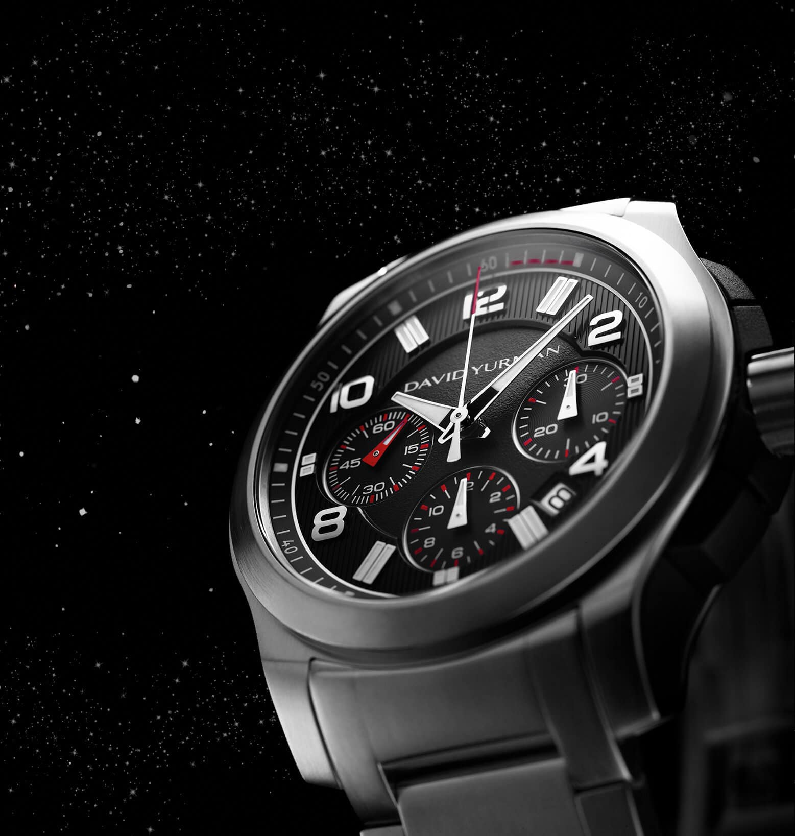 A color photograph shows a close-up shot looking up at the face of a David Yurman men's Revolution chronograph standing upright in front of a starry night sky. The watch is crafted with a stainless-steel case and a black-and-silver dial.