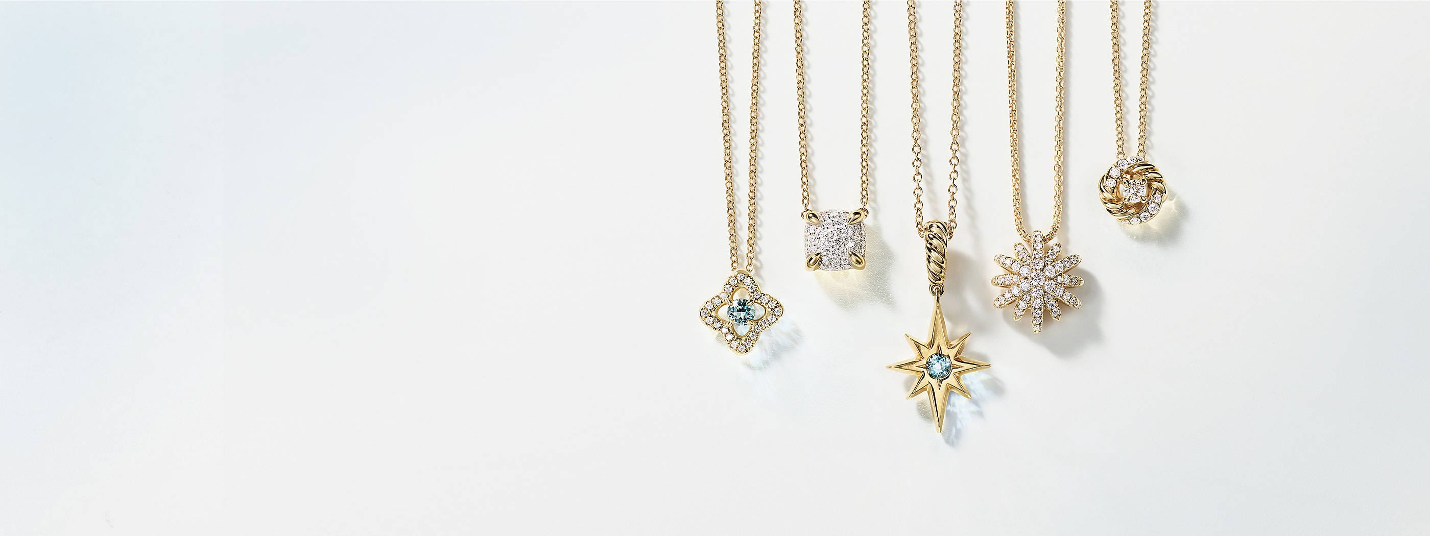 A color photograph shows a horizontal row of five David Yurman charm necklaces hanging in front of a light blue and white background. The women's jewelry is crafted from 18K yellow gold with or without pavé diamonds and aquamarine center stones. The pendants come in various shapes such as a star, circle, cushion and quatrefoil.