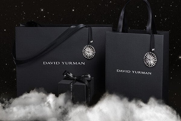 A color photo shows a large and a small David Yurman shopping bag standing behind a David Yurman gift box on a white cloud in a starry night sky. The black gift bags are each adorned with a Starburst ornament on a black cord with silver accents. The David Yurman logo is printed in white in the center of each bag. The black ring box is wrapped with a black ribbon featuring the David Yurman logo printed in white.