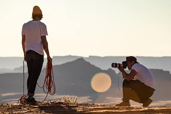 A color photo shows photographer/director Jimmy Chin crouching down and aiming his camera at climber Sam Elias, who is holding climbing ropes. Both are outdoors in Utah's Moab desert.